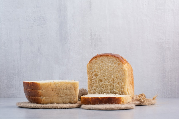 Slices of fresh bread on stone surface