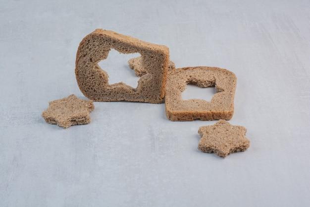 Fette di pane integrale fresco su sfondo marmo.
