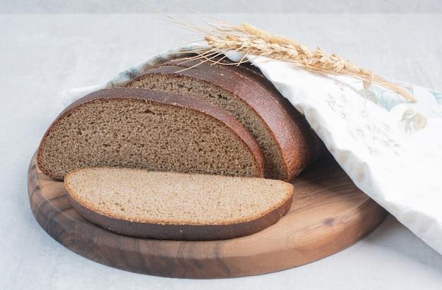 Fette di pane integrale fresco sulla tovaglia.