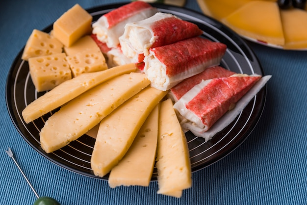 Slices of fresh cheese near snacks on plate on table
