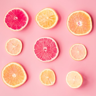 Slices of fresh citrus fruits on pink background