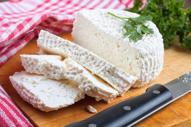 Slices of fresh cottage cheese on wooden cutting board