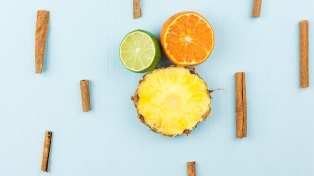 Slices of fresh exotic fruits among cinnamon