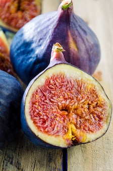 Slices of fresh figs on a wooden background