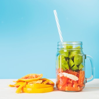 Slices of fresh fruits in jar against blue wall