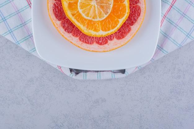 Fette di pompelmo, arancia e limone freschi sulla zolla bianca.
