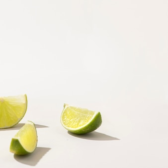 Slices of fresh green lime on white table
