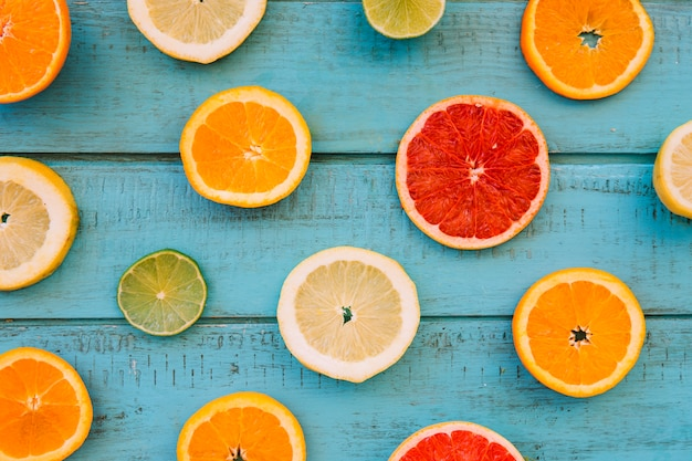 Slices of fresh juicy citrus fruits on blue wooden plank