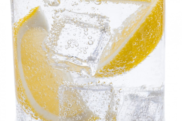 Slices of fresh juicy yellow lemon with ice in clear water.