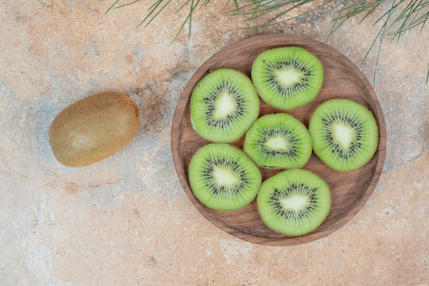 Slices of fresh kiwi on wooden plate.