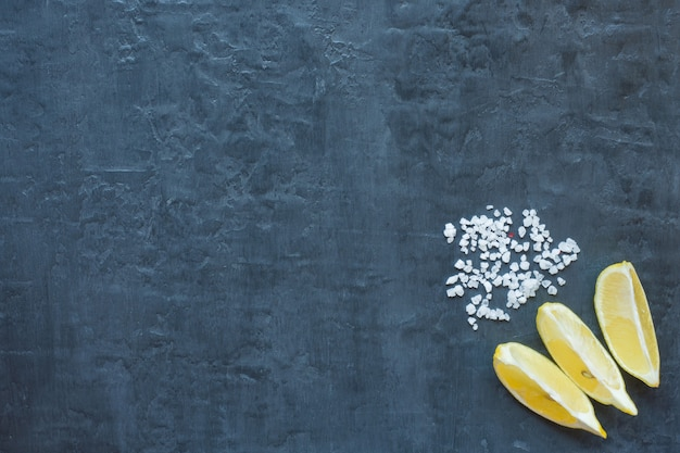 Slices of fresh lemon and coarse salt on dark background with copy space