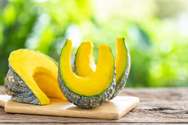 Slices of fresh pumpkin on wooden table. food concept