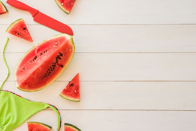 Slices of fresh red fruits near swimsuit
