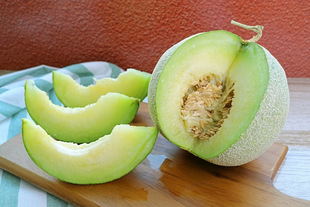 Slices of  fresh ripe sweet and aromatic muskmelon with whole fruit on a wooden cutting board
