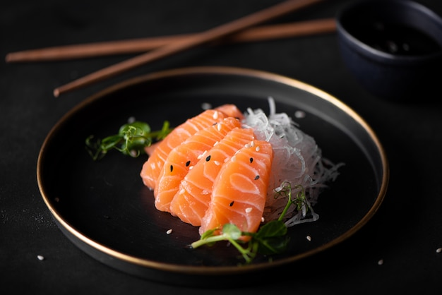 Slices of fresh salmon with radish and soy sauce