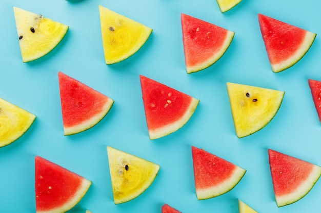 Slices of fresh slices of yellow and red watermelon on a blue . view from above
