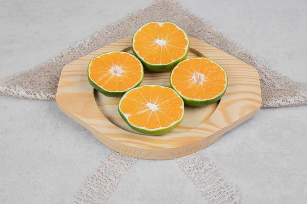 Slices of fresh tangerines on wooden plate. high quality photo