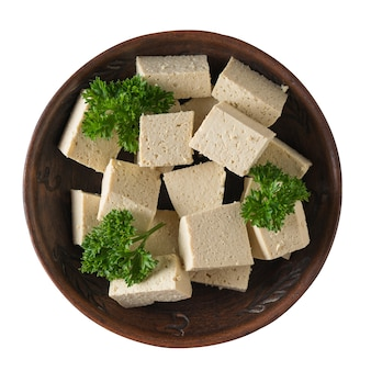 Slices of fresh tofu cheese in a clay bowl isolated on a white surface. soy cheese. vegetarian product. flat lay.