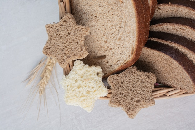 Fette di vari tipi di pane fresco su sfondo di marmo.