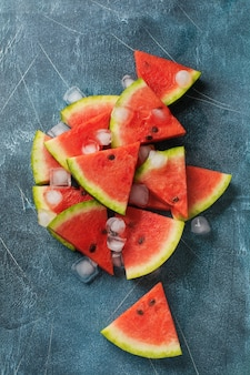Slices of fresh watermelon with ice on a blue concrete background. detox and vegetarian concept. top view, copy space, banner