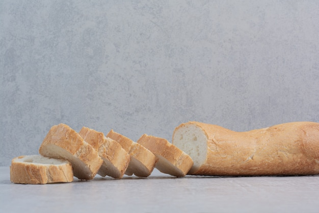 Slices of fresh white bread on marble background.