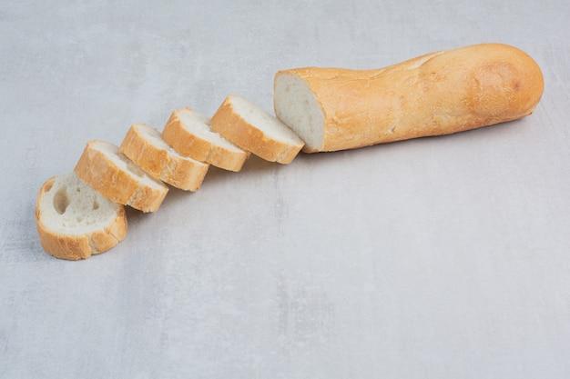 Fette di pane bianco fresco su sfondo marmo.