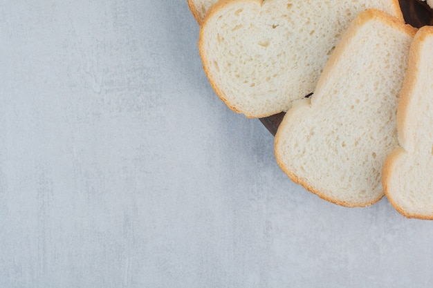 Slices of fresh white breads on marble background.