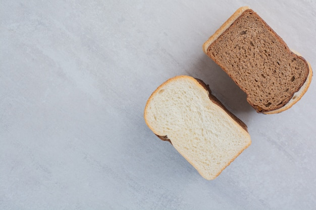 Slices of fresh white and brown breads on marble background.