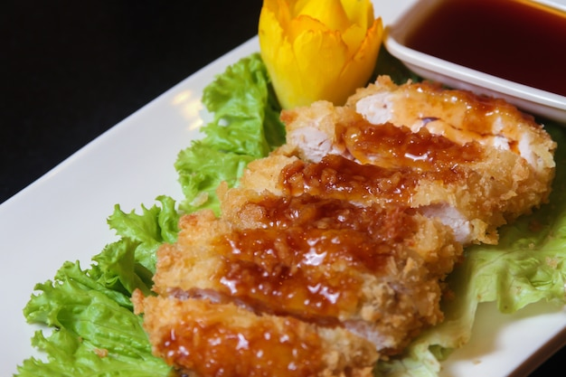 Slices of fried chicken decorated with lettuce and a small bowl of sauce