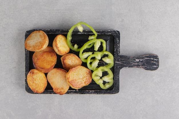 Fette di patate fritte e peperoni sul bordo nero.