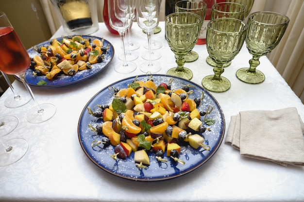Slices of fruit in a large assortment on skewers lie on a white plate.