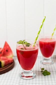 Slices of fruits on board and glasses with cocktail on napkin near plants
