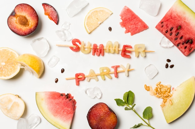 Slices of fruits between ice and summer party title