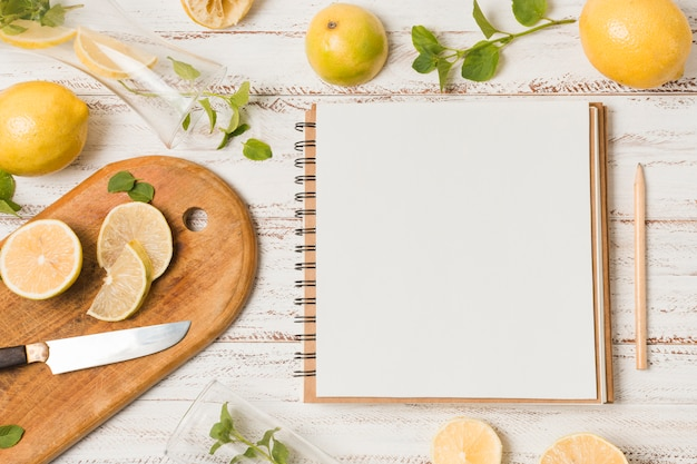 Slices of fruits near knife between herbs and notebook