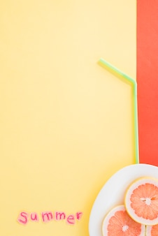 Slices of fruits on plate near straw and summer word