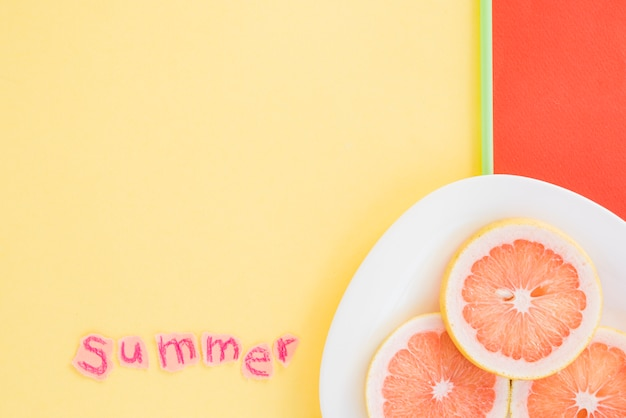 Slices of fruits on plate near summer word