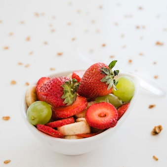 Slices of fruits in white bowl spread with oats on white backdrop