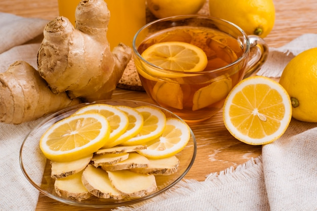 Slices of ginger and lemon on a plate and cup of tea with lemon  on a wooden table