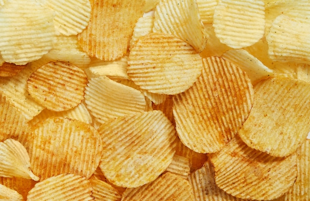 Slices golden chips with stripes lying slides background texture. view from above