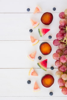 Slices of grapefruit; watermelon; blueberries; plum and grapes on wooden white desk
