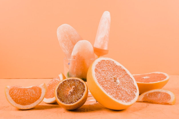 Slices of grapefruits and oranges with popsicles on an orange background