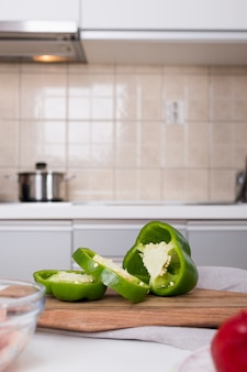 Slices of green bell pepper on chopping board in the kitchen