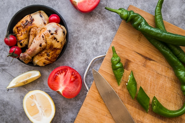 Slices of green chilies and knife on wooden chopping board with grilled chicken; tomato; lemon over concrete background