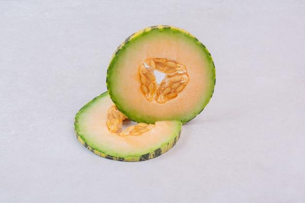 Fette di melone verde su bianco.