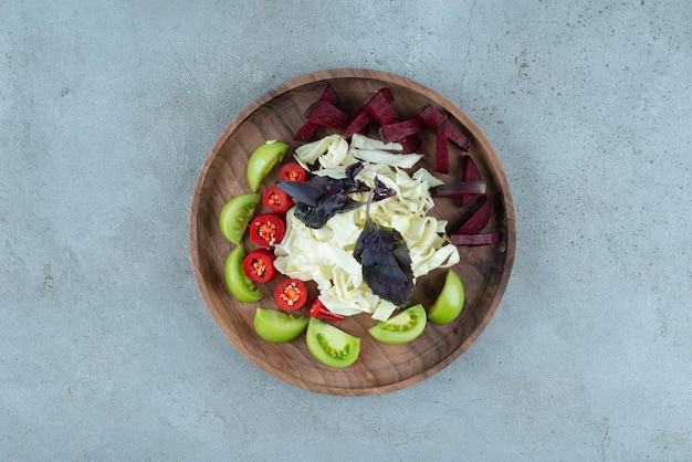 Fette di pomodoro verde e cavolo tritato sul piatto di legno.
