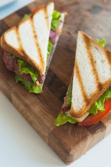 Slices of grilled sandwich on wooden chopping board