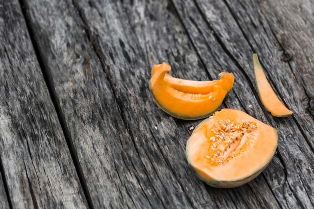 Slices and halved of musk melon on an old wooden table