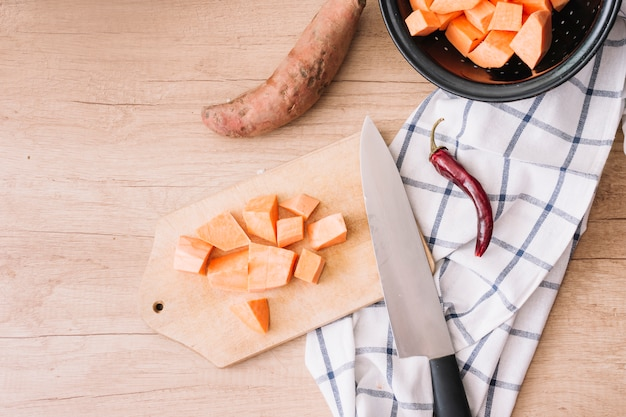 Slices of healthy sweet potato on chopping board with knife; red chili and tablecloth on wooden table