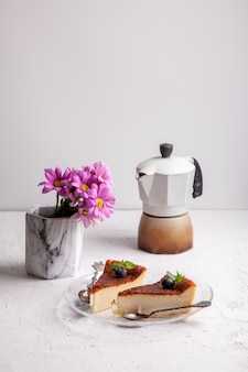 Slices of homemade basque burnt cheesecake with blueberries and mint leaves, a geyser coffee maker, lilac flowers in a vase on a light background