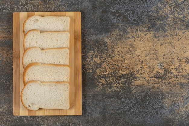 Slices of homemade bread on wooden board.
